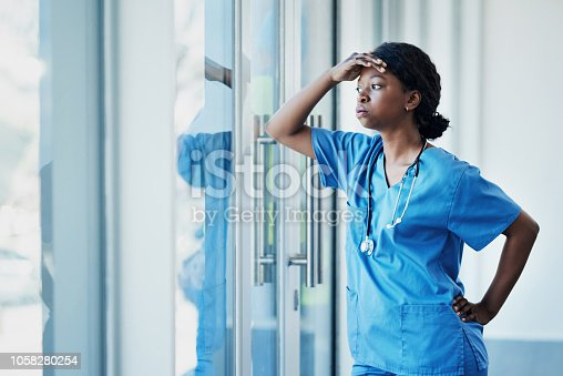Shot of a young female nurse looking stressed out while standing at a window in a hospital