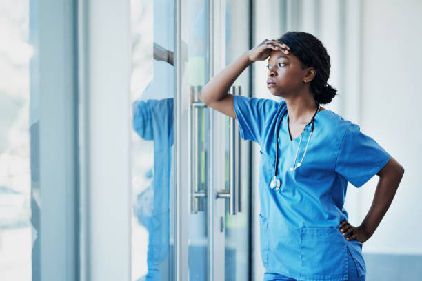 Doctors face heavy levels of stress too Shot of a young female nurse looking stressed out while standing at a window in a hospital overworked stock pictures, royalty-free photos & images