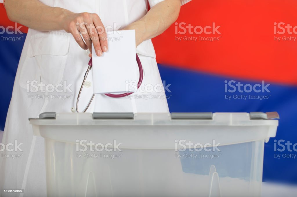 Doctor's hand casts ballot paper in the ballot box. stock photo