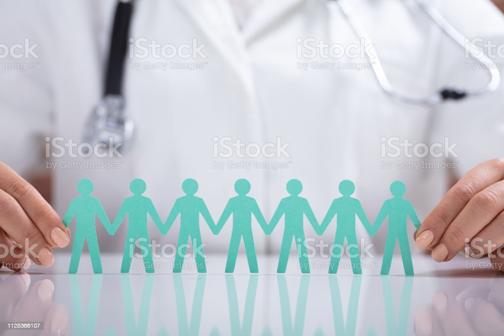 Close-up Of Doctor\'s Hand Holding Chain Of Human Figure Holding Hand...