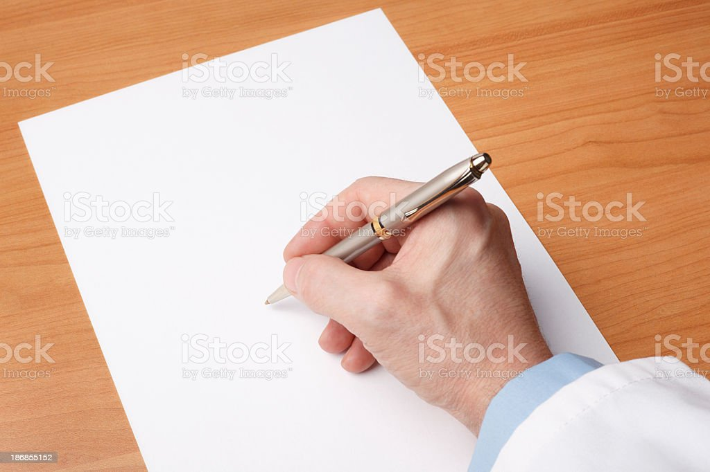 Doctor's hand writing on blank sheet of paper royalty-free stock photo