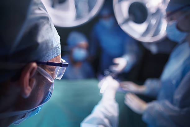 Doctors handling equipment in hospital operating room stock photo