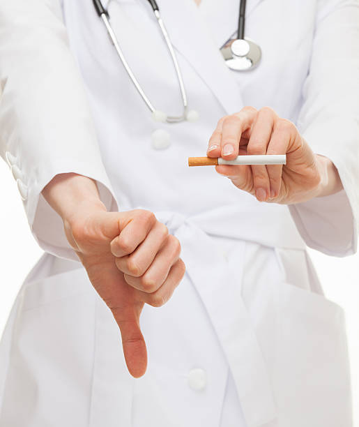 Doctor's hands showing disabling gesture and holding a cigarette Doctor's hands showing disabling gesture and holding a cigarette, healthy lifestyle concept deleterious stock pictures, royalty-free photos & images