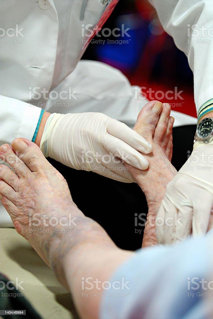 Doctor's hands touching diabetic patient's foot stock photo