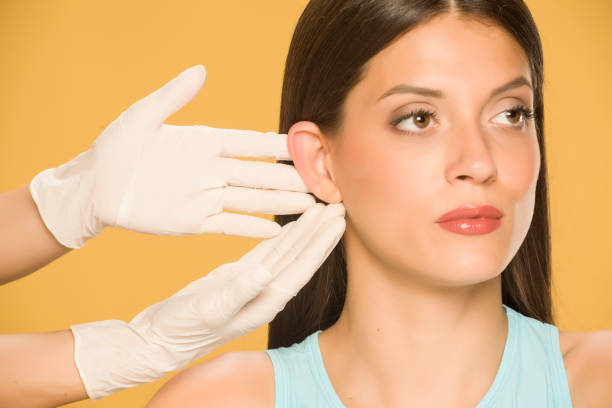 Doctor's hands touching the nose of a young woman on yellow background stock photo