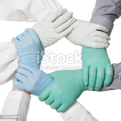 Doctors joining their hands in gloves together, making a circle. Isolated on white. Teamwork (unity) concept.