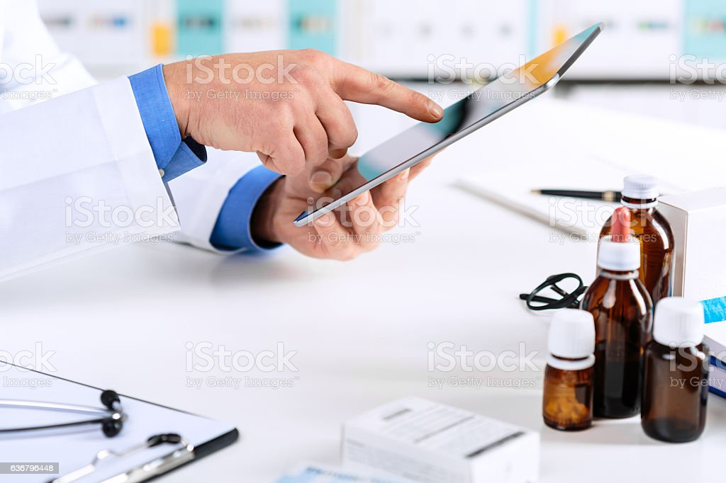 Doctor's hands working on a digital tablet at his Office – Foto