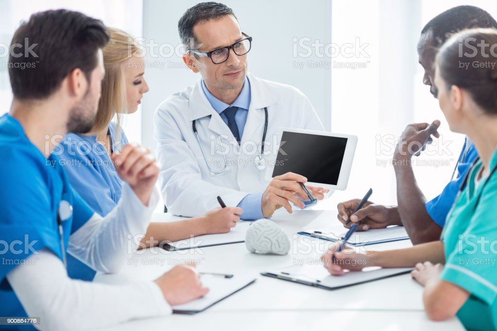 doctors having conversation and looking at tablet stock photo