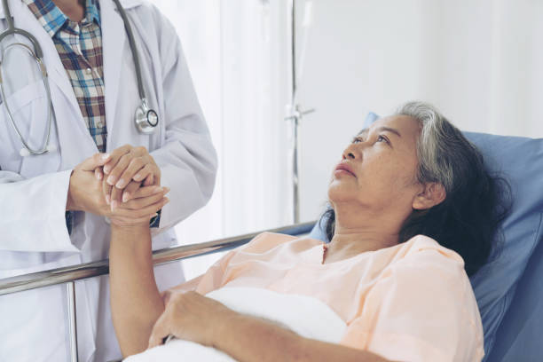 Doctors hold hands to encourage  Elderly senior woman patients in the hospital- senior female medical and healthcare concept stock photo