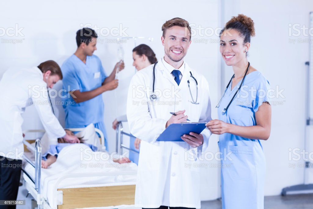 Doctors holding clipboard and smiling at camera royalty-free stock photo