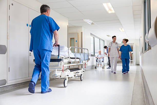 doctors hospital corridor nurse pushing gurney stretcher bed - hospital stock pictures, royalty-free photos & images