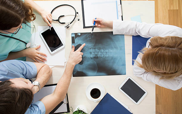 Doctors interpreting x-ray image Doctors sitting around the table and interpreting x-ray image medical x ray stock pictures, royalty-free photos & images