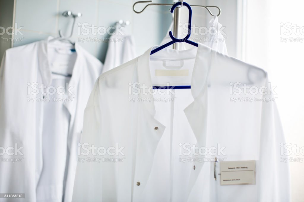 Doctor's lab coat on hanger in laboratory stock photo