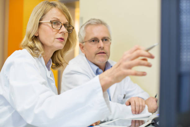 Doctors looking at computer on desk in hospital stock photo