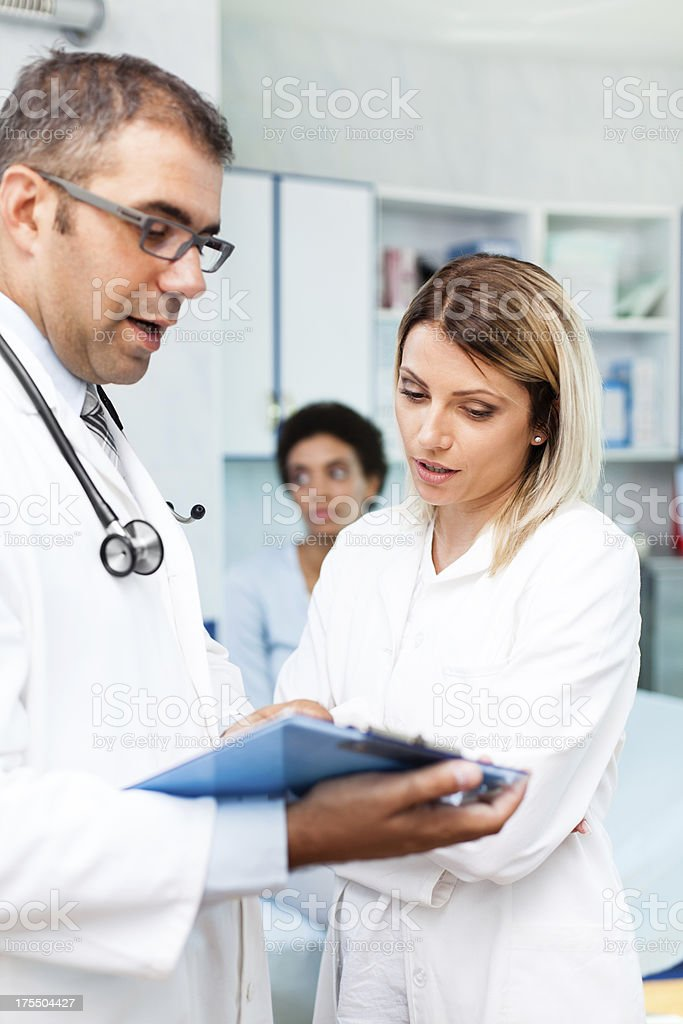 Male and female doctor looking at medical records while young female...