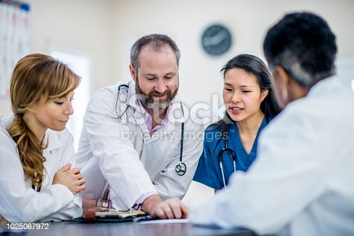 A multi-ethnic group of doctors are indoors in an office. They are gathered around a table to have a meeting.