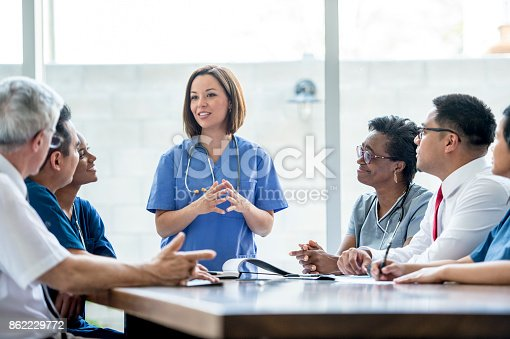 A multi-ethnic group of medical staff are indoors in a hospital. They are wearing medical clothing. A Caucasian female doctor is giving a presentation to the others.