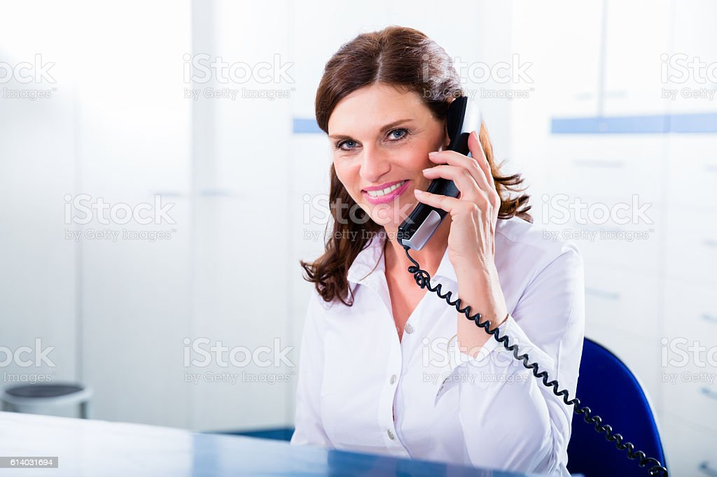 Doctors nurse with telephone in front desk – Foto