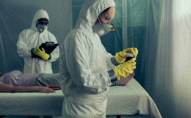 Doctors preparing medication for sick woman Doctors with bacteriological protection suits preparing medication for sick woman epidemic stock pictures, royalty-free photos & images
