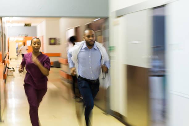 Médecins en cours d'exécution dans un couloir de l'hôpital - Photo