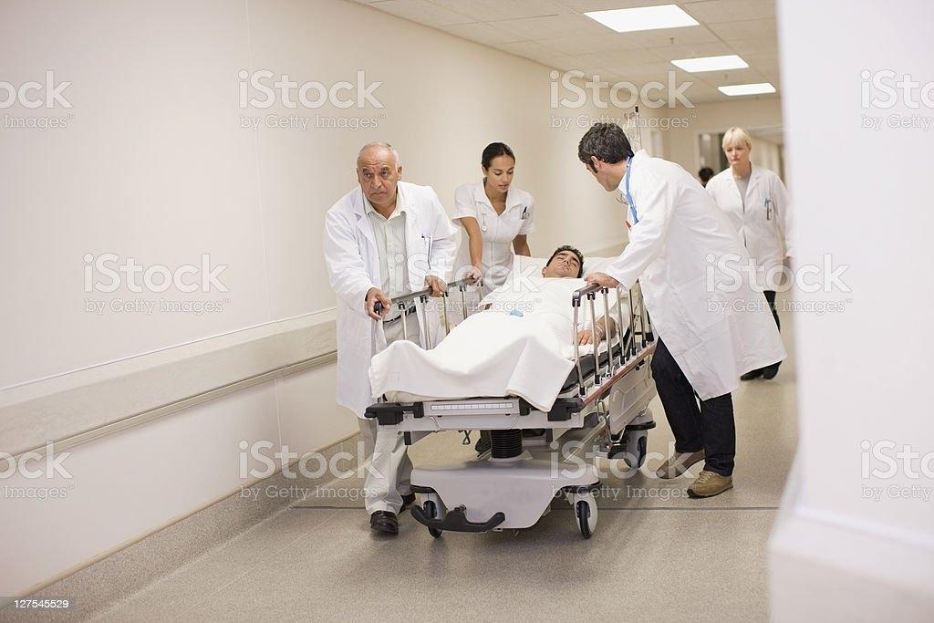 Doctors rushing patient down hallway stock photo