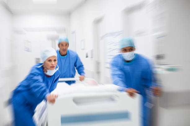 Doctors rushing patient to surgery Nurse and doctor in a hurry taking patient to operation theatre. Patient on hospital bed pushed from surgeon to emergency theatre. Team of doctors and surgeon rushing patient. accidents and disasters stock pictures, royalty-free photos & images