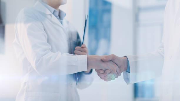Médicos, apertando as mãos no escritório - foto de acervo