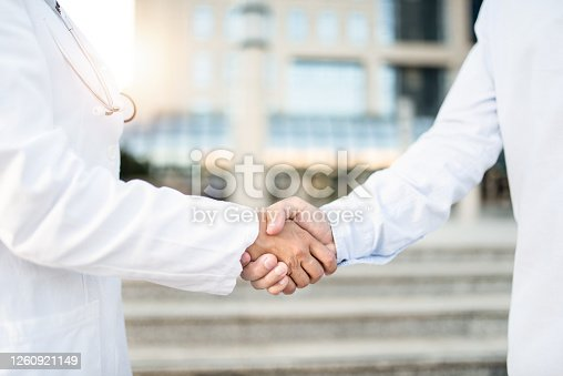 Unrecognizable doctors shaking hands outdoors in front of hospital.