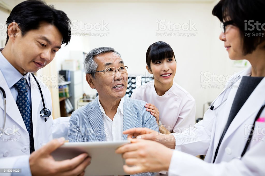 Doctors showing digital tablet to smiling senior man in hospital stock photo