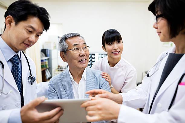 Doctors showing digital tablet to smiling senior man in hospital ストックフォト