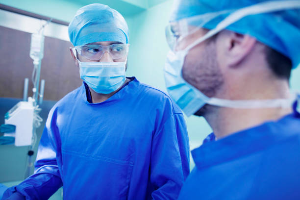 Doctors talking during surgery in operating room stock photo