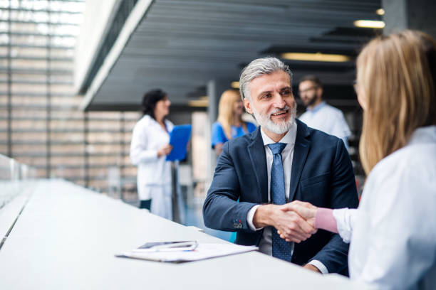Doctors talking to pharmaceutical sales representative, shaking hands. stock photo