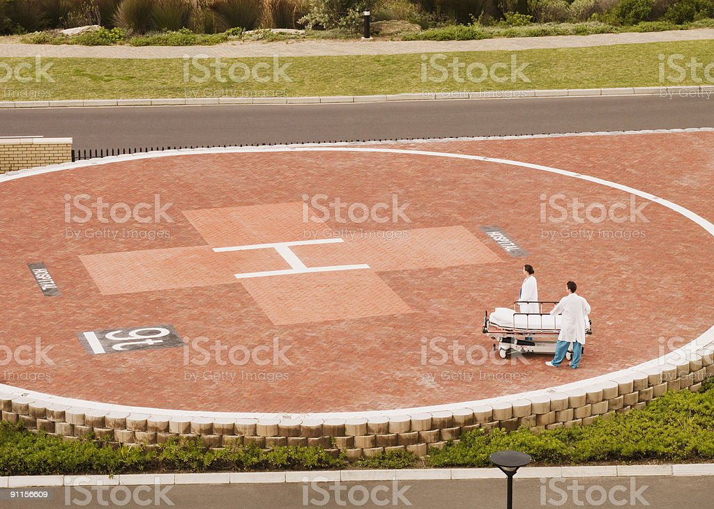 Doctors waiting for helicopter with gurney stock photo