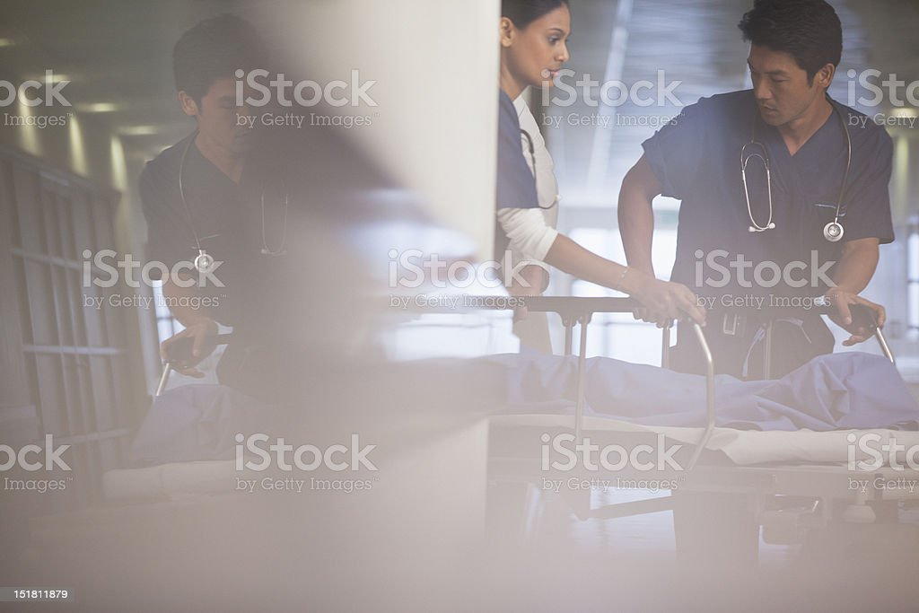 Doctors wheeling patient on gurney in hospital corridor royalty-free stock photo
