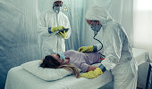 Doctors with bacteriological protection suits attending a patient infected with a virus