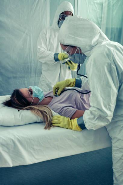 Ärzte mit bakteriologischem Schutzanzug bei Patientenbesuch – Foto