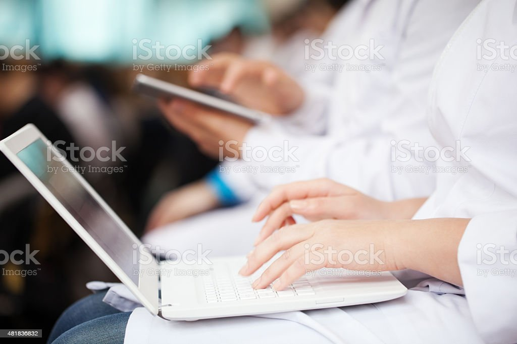 Doctors with laptop and pad on the conference stock photo