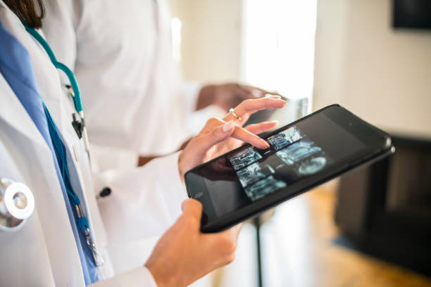 doctors working with digital tablet - medical research stock photos and pictures