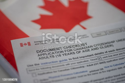 Document check list application for canadian citizenship next to Canadian flag, close up view.