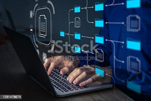 istock Document Management System (DMS) being setup by IT consultant working on laptop computer in office. Software for archiving, searching and managing corporate files and information. Business processes 1291478674