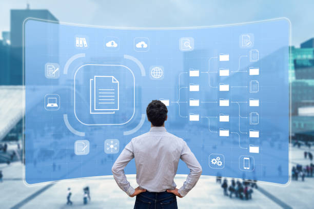 Document Management System (DMS) used to archive, search and manage corporate files and information in enterprise along business processes. Concept with manager looking at screen stock photo
