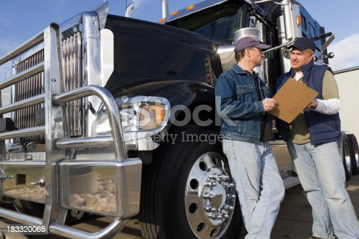 A royalty free image from the trucking and transportation industry of two truck drivers reviewing documents.