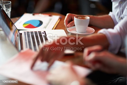 Close up view of male hands while signing contract in a cafeteria. Laptop computer and paper documents are on the table.