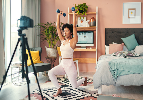 Shot of a young woman recording herself while exercising at home
