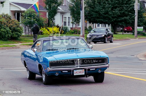 Truro, Nova Scotia, Canada - July 14, 2019 : 1969 Dodge Charger entering Annual Blaikies Mopar Show & Shine. Male driver and lady passenger can be seen inside the classic muscle car.
