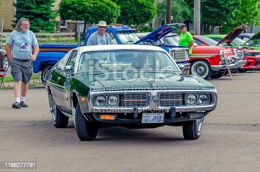 Truro, Nova Scotia, Canada - July 14, 2019 : 1974 Dodge Charger SE leaving the Annual Blaikies Mopar Show & Shine. Car show attendant walks behind the classic Dodge.