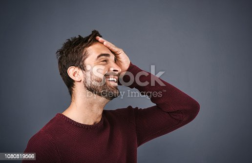 Studio shot of a handsome young man looking relieved against a gray background