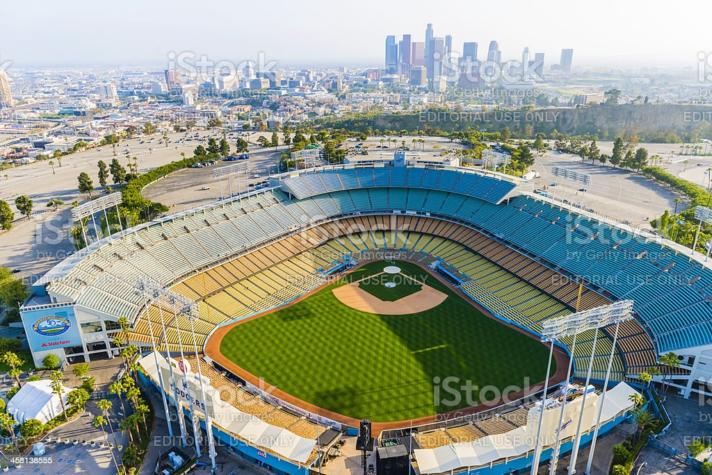 """Dodger Stadium and Los Angeles skyline cityscape panorama aerial """"Los Angeles, California, USA - April 29, 2012: Aerial view from helicopter of Los Angeles Dodger Stadium in Elysian Park, with the skyscraper skyline of Los Angeles in the smoggy background distance. The Stadium is just north of downtown Los Angeles and is the home of the Los Angeles Dodger major league baseball team. The stadium in this photo is empty at a time when no game is being played."""" Aerial View Stock Photo"""