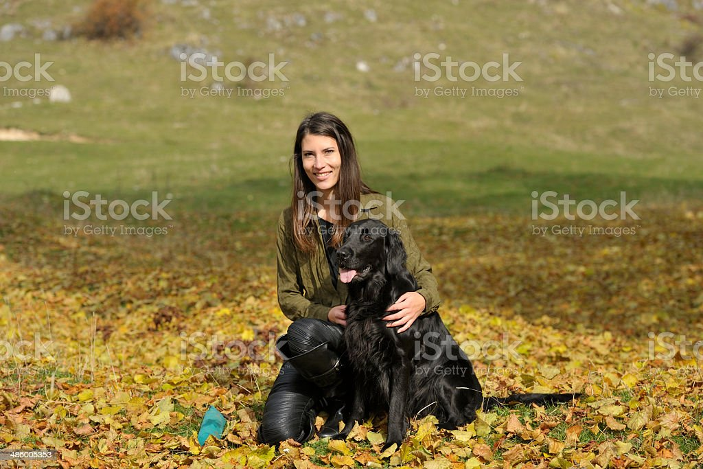 Dog and woman, autumn leaves and blue toy royalty-free stock photo