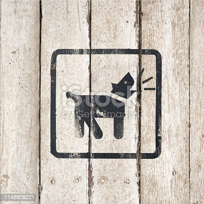 Guard dog inside icon. Dog Barking icon. Button image on wooden background. Barking dog silhouette in black color. Barking dog sign on a white wooden background. Part of a series